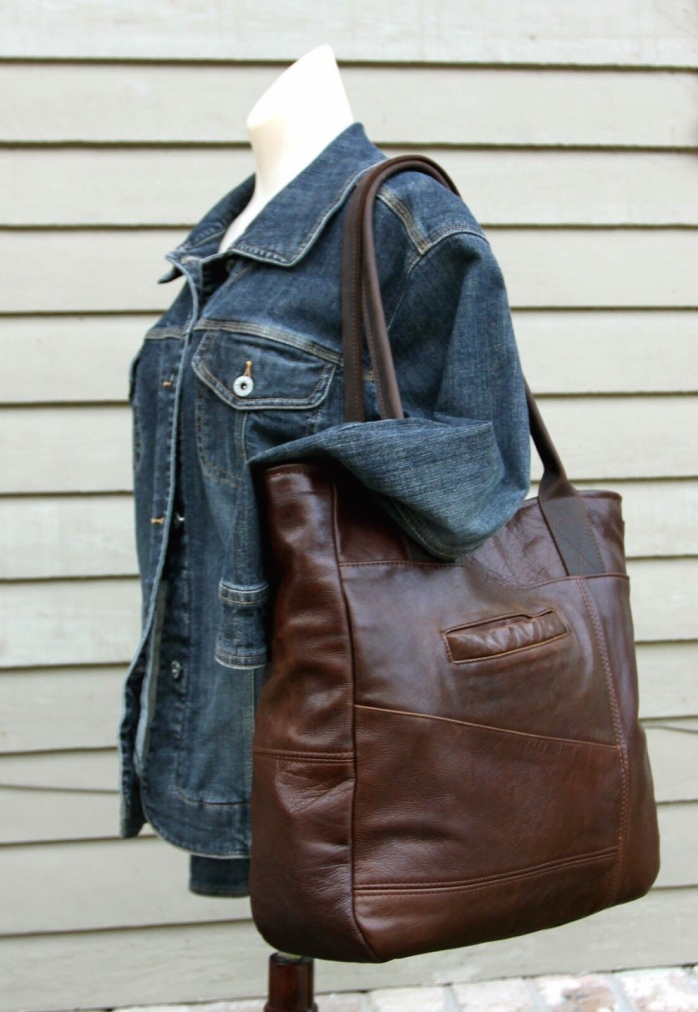 Image of person holding a large brown leather tote bag over the shoulder